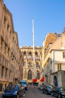 프랑스. 파리의 여름 화창한 날. 주차된 차가 있는 좁은 거리. 크레인 화재 후 노트르담 복원