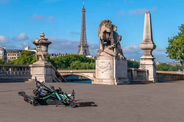 Франция. летний солнечный день в париже. набережная сены с видом на эйфелеву башню. куча прокатных электросамокатов на тротуаре