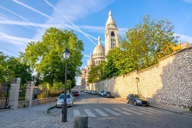 Франция. летний солнечный день в париже. крыши аббатства сакре-кер на фоне голубого неба. несколько машин припаркованы на мощеной улице