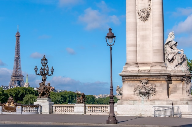 France. summer sunny day in paris. historic column and lanterns on the bridge alexandre iii across the river seine. eiffel tower in the distance