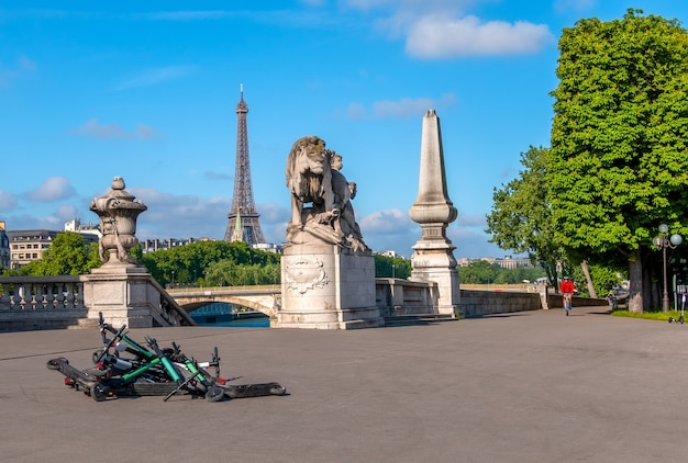 France. summer sunny day in paris. seine embankment overlooking the eiffel tower. heap of rental electric scooters on the pavement
