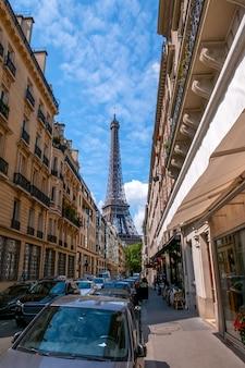 Франция. солнечный летний день в париже. много машин и уличных кафе. эйфелева башня далеко