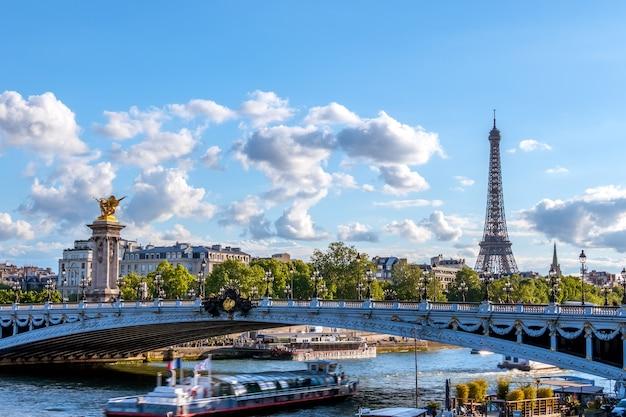 Франция. солнечный летний день в париже. прогулочный катер под мостом александра iii через сену. эйфелева башня