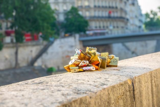 Франция. солнечное летнее утро в париже на набережной сены. связка замков, прикованных к гранитному парапету