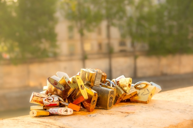 France. sunny summer morning in paris on the embankment of the river seine. several padlocks are chained to a granite parapet