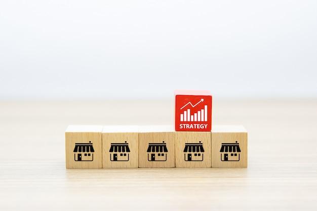 Франчайзинговый бизнес. деревянный игрушечный блог в форме куба, сложенный с магазином значков франшизы маркетинга роста бизнеса и концепции организационного управления.