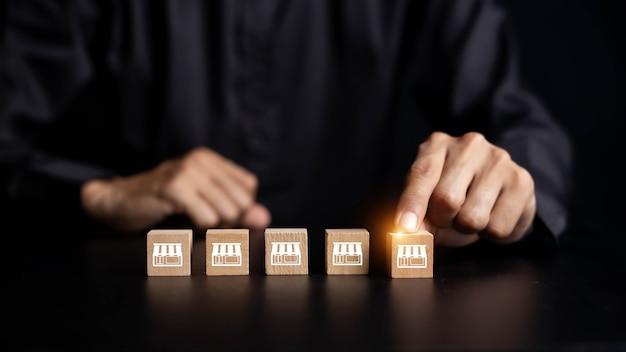 フランチャイズビジネス、ビジネスマンの手はフランチャイズマーケティングアイコンストアと木製のブログを選択します。