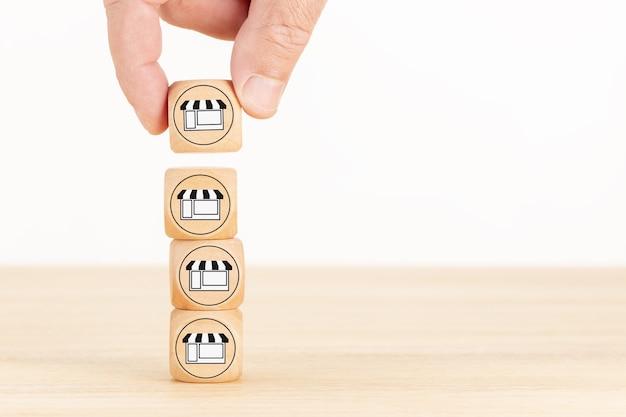 프랜차이즈 사업 개념. 사업가 손 프랜차이즈 마케팅 아이콘 저장소와 나무 블록을 선택합니다. 공간 복사