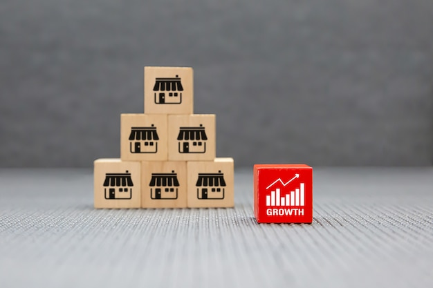 Franchise business icons store on wooden toy blocks stacked in pyramid shape with graph symbol.