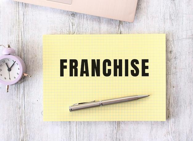 나무 작업 테이블에 누워 노트북에 쓰여진 프랜차이즈 텍스트 프리미엄 사진