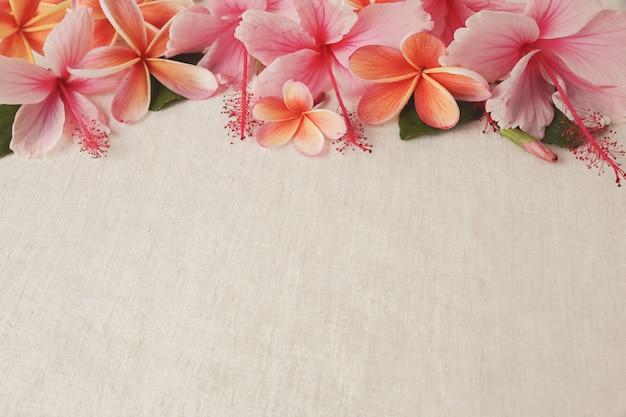 Frangipani, plumeria, hibiscus flowers on linen