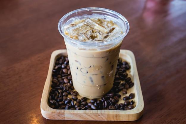 Холодный кофейный напиток frappe или frappuccino в деревянном подносе с кофейным зерном на деревянном столе