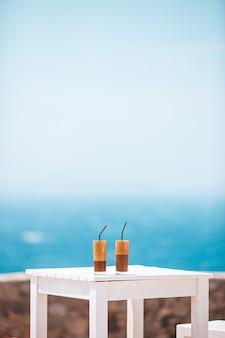 프라페, 해변에서 아이스 커피. 키가 큰 유리 배경에 여름 아이스 커피 프라푸치노, 프라페 또는 라떼 비치 바의 바다