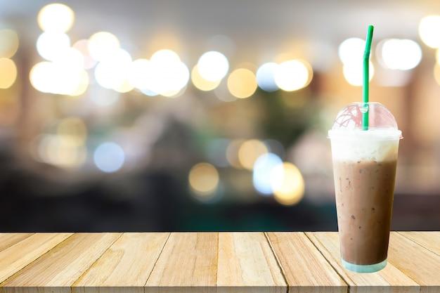 Ледяной кофе. кофе frappuccino и размытое кафе с боке светлым фоном.