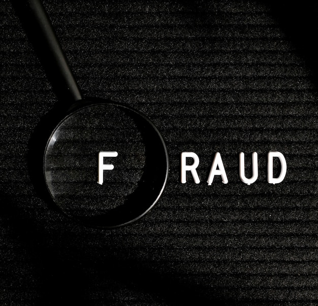 Fraud word with letter in a magnifying glass top view