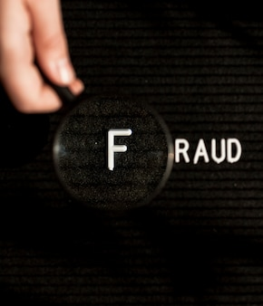 Fraud word with letter in a magnifying glass