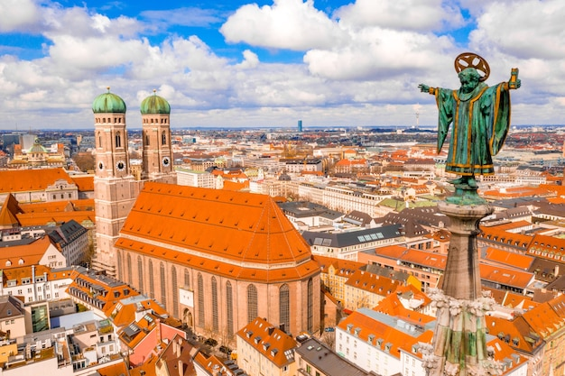 Frauenkirche surrounded by buildings under the sunlight and a cloudy sky in munich, germany
