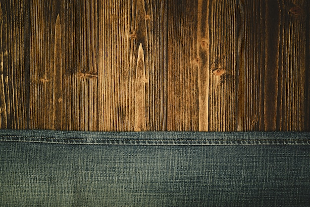 Frayed jeans or blue jeans denim collection on wood