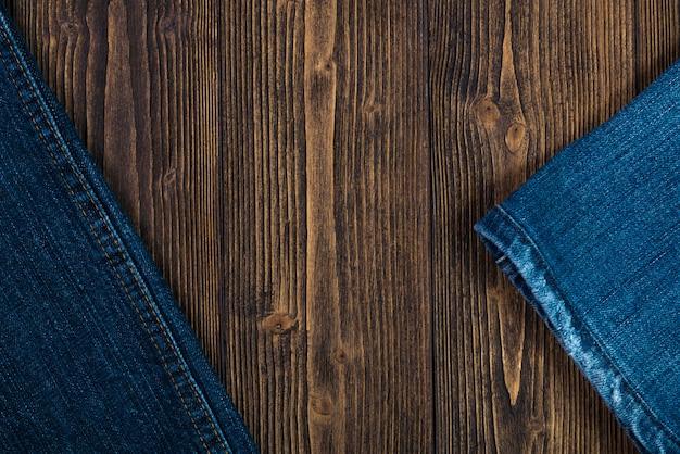 Frayed jeans or blue jeans denim on dark wood