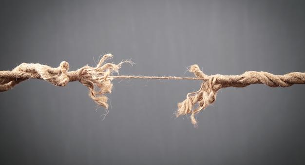 灰色の背景で擦り切れたロープが壊れようとしています。危険