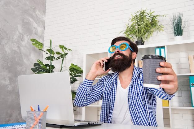 プロジェクトを管理するフリーク。ハイパフォーマーの感情的および精神的構成。オフィスフリーク。職場での奇妙な。コーヒーを飲みながら電話をしている男フリーククレイジーオフィスマネージャー。生産的な日。