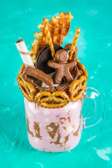Freakshake from pink smoothie, cream. monstershake with a chocolate man, cane