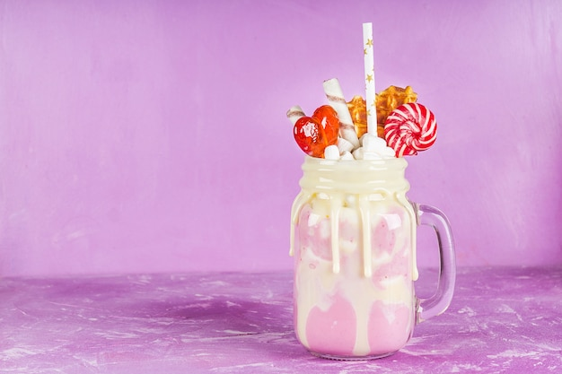 Freakshake from pink smoothie, cream. monstershake with lollipops, waffles and marshmallow.