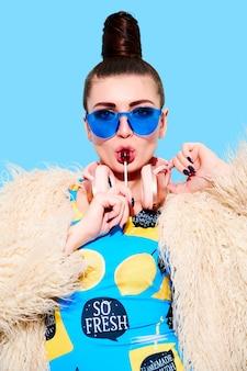 이상한 힙 스터 dj 소녀는 수영복과 모피 코트를 입고 롤리팝을 핥고 밝은 파란색 벽에 분홍색 헤드폰으로 음악을들을 수 있습니다.
