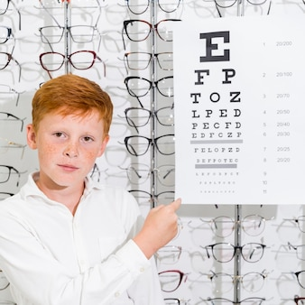 Freckle boy looking at camera and pointing at snellen chart in optics showroom