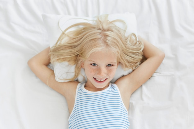 Freckled blonde girl lying in bed, having pleased expression while rejoicing strart of new day, having weekends, not going to school. smiling happy child having good relaxation in comfortable bed