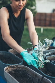 Freckled caucasian woman repotting flowers at home in the backyard wearing gloves and smile