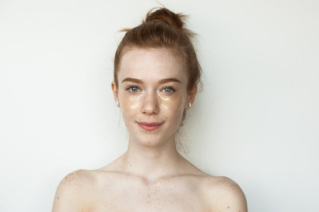Freckled caucasian woman with red hair is wearing hydrogel eye patches posing on a white wall with naked shoulders