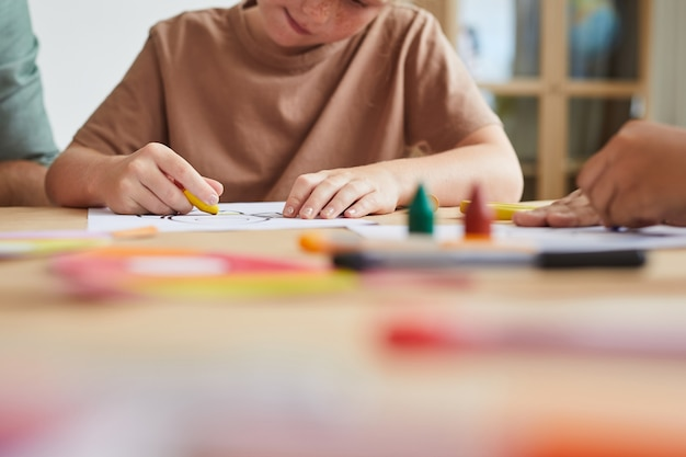 Веснушчатая девочка рисует картины мелками во время урока рисования в дошкольном учреждении