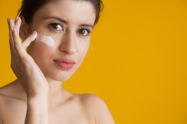 Freckled woman applying anti aging cream on her face is posing with naked shoulders on a yellow wall