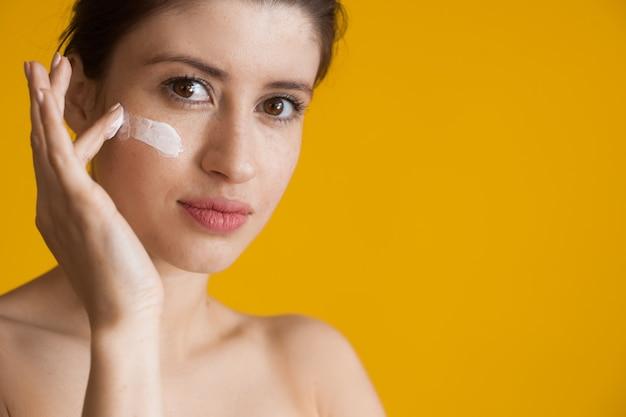 Веснушчатая женщина, нанося антивозрастной крем на лицо, позирует с обнаженными плечами на желтой стене