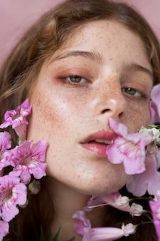 ピンクの花を持っているそばかすのある女性