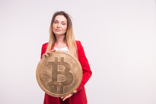 Freckled woman holding big bitcoin on white background. cryptocurrency investment concept.