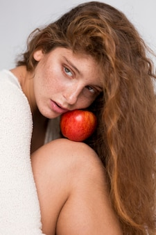 Freckled woman posing with red apple