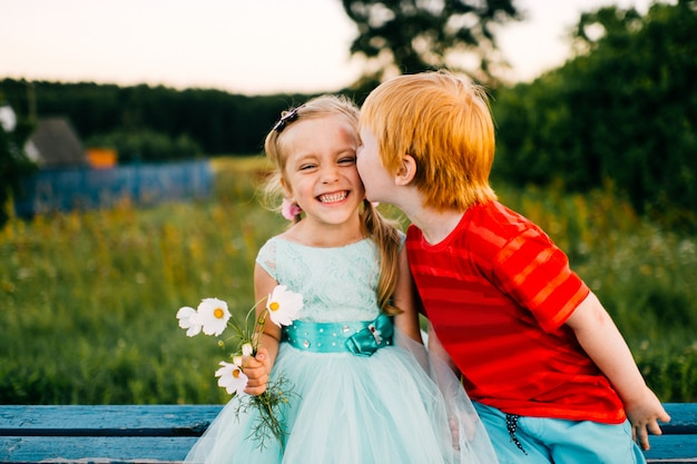 Freckles boy kising little shy beautiful girl in blue holiday dress outdoor on road in countryside at sunset in nature.