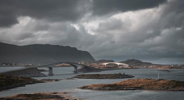 Fredvang 다리와 우울한 구름 아래 가을에 lofoten islands 노르웨이의 주변 산과 바다