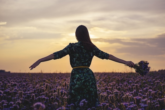 Free brunette with open hands enjoys the sunset in a flower field.