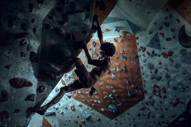 Free climber climbing artificial boulder indoors