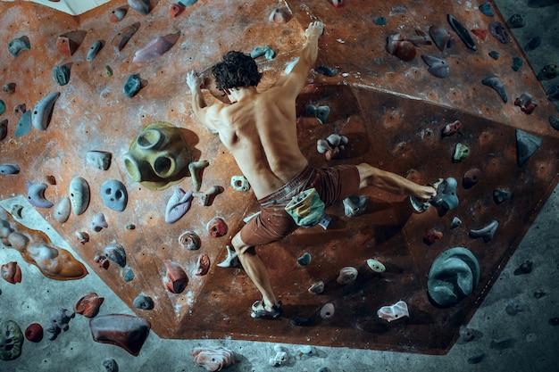 屋内で人工の岩を登る無料の登山家の若い男。