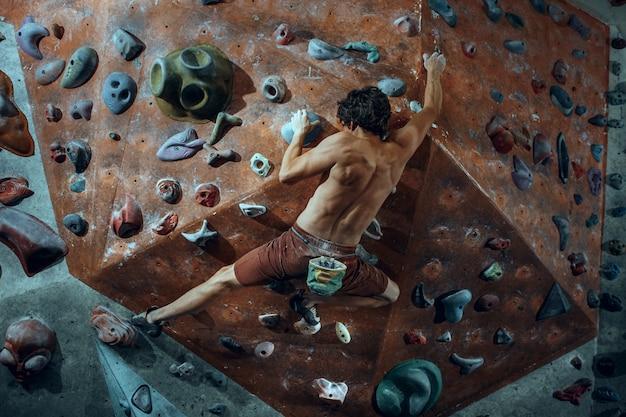 Free climber young man climbing artificial boulder indoors.
