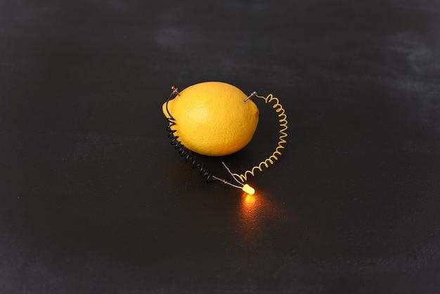 Генератор электричества бесплатной энергии с использованием лимона. Premium Фотографии