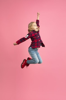 Free and happy, flying, jumping high. caucasian girl's portrait on pink studio wall.