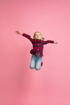 Free and happy, flying, jumping high. caucasian girl's portrait on pink wall. beautiful model with blonde hair. concept of human emotions, facial expression, sales, ad, youth, childhood.