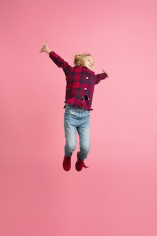 Free and happy, flying, jumping high. caucasian girl's portrait on pink wall. beautiful model with blonde hair.