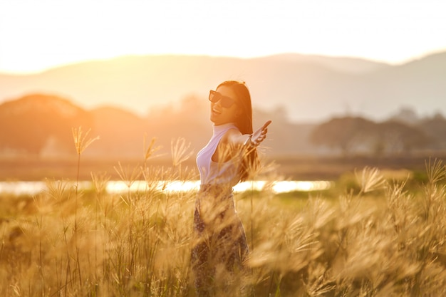 Free happy woman enjoying sunset. beautiful woman in white dress embracing the golden sunshine glow of sunset with arms outspread and face raised in sky enjoying peace, serenity in nature