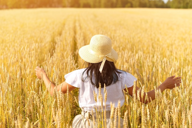Free and happy woman in a flying dress and a hat on a wheat field. freedom, joy concept.